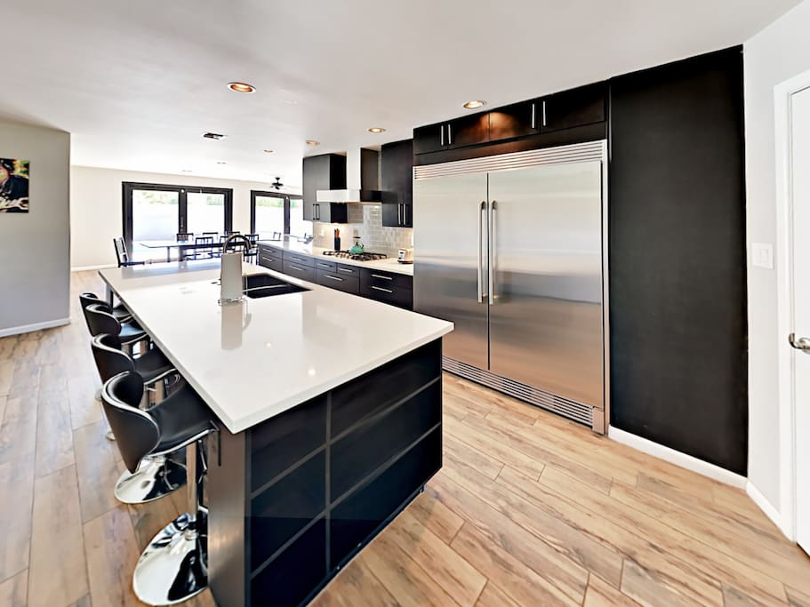 Prepare home cooked meals in the gourmet kitchen with quartz countertops, stainless steel appliances, and a gas range.