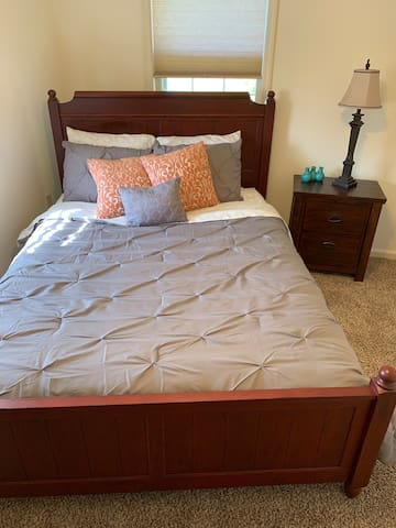 Room with a queen bed, dresser, night stand, alarm clock, and ceiling fans.