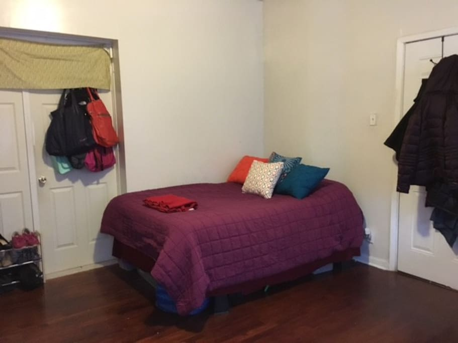 Queen sized bed. Private entrance into room on the right. Door to kitchen and bathroom on the left.