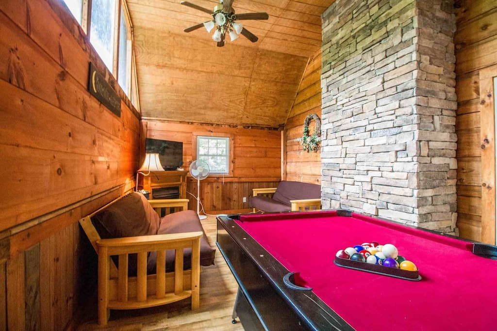 On the main level, you'll find a game room with a pool table, flatscreen tv, and two futons for additional sleeping