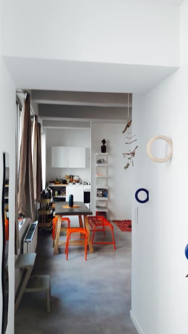 Entrée dans la maison, à gauche d'immenses fenêtres, et devant le salon, puis la cuisine ouverte.