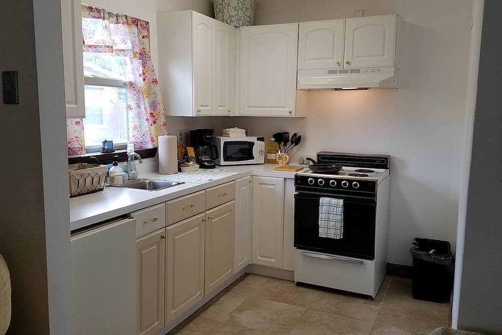 private kitchen with oven, 2 mini-fridges, sink, microwave, toaster, mini fridge, coffee maker with coffee tea and creamer, plates, flatware, cooking utensils, bowls, cups, napkins, cooking oil, salt and pepper, mugs...