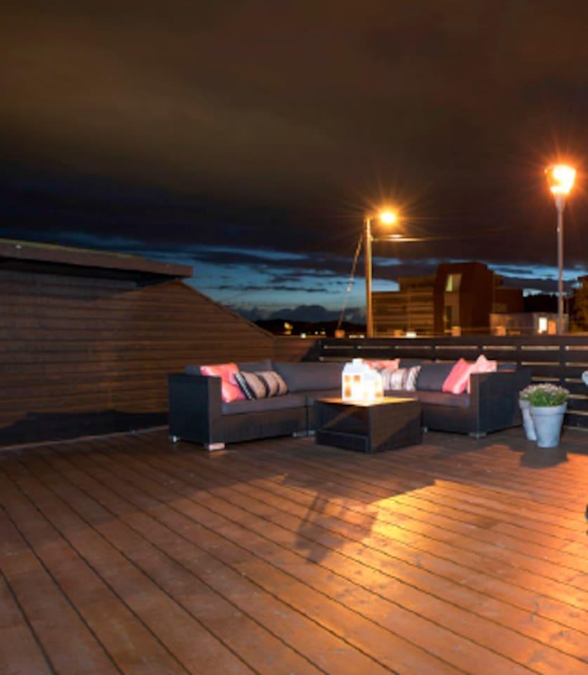 Stor og usjert terrasse med stor sittegruppe, gassgrill og spisebord med 8 stoler