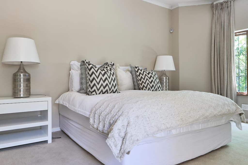 Spacious master bedroom with deluxe super king bed, large bedside tables and dressing table. The bedroom also has direct  access to the garden.