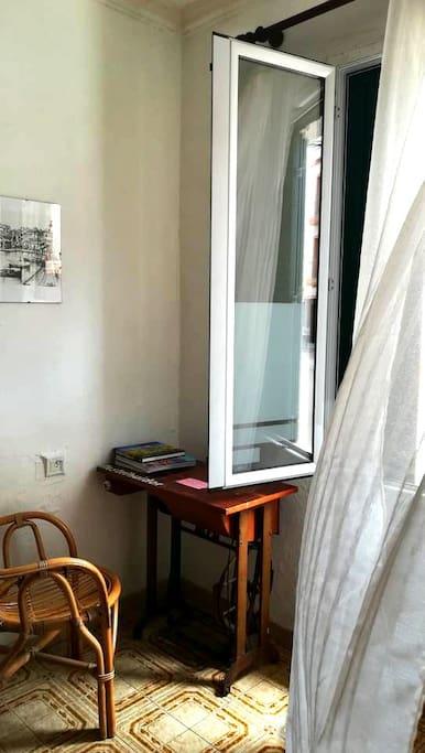 Una mesa,silla y el ventanal con cortina