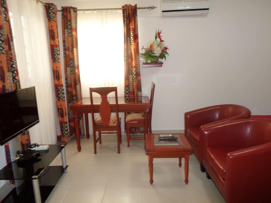 Le coin salon/salle à manger est équipée de 2 fauteuils club + table basse carrée et d'1 table + 2 chaises pour les repas ou pour travailler