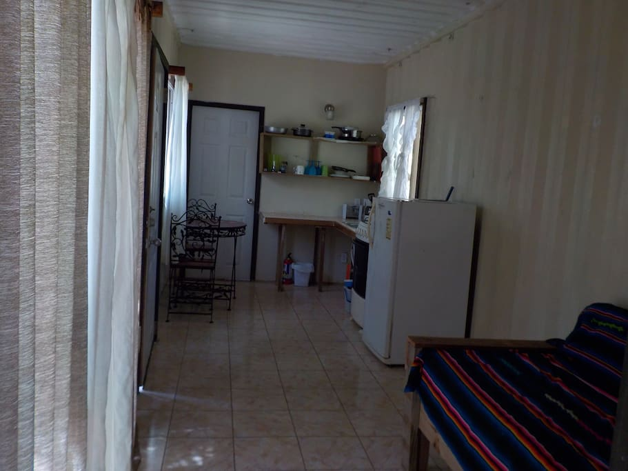 The kitchen area has fridge, stove/oven, toaster, coffee maker, table and chair set and kitchen essentials.