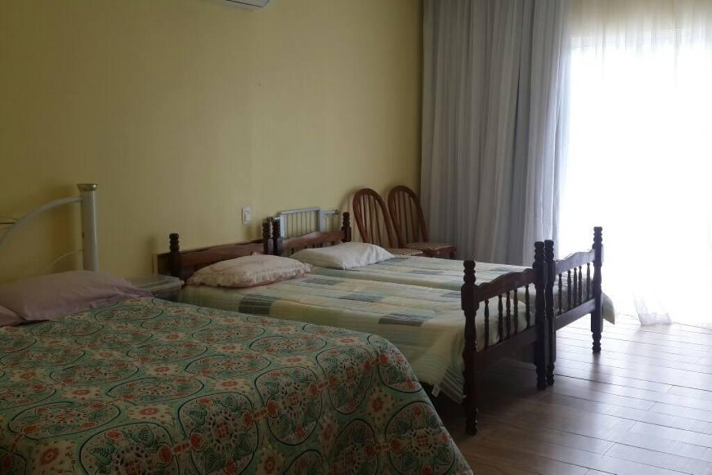 Quarto com cama de casal e 2 de solteiro. A pedido podemos tirar as de solteiro.
