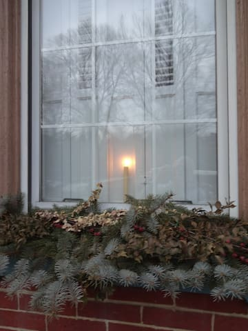 Holiday window greens and welcome candle