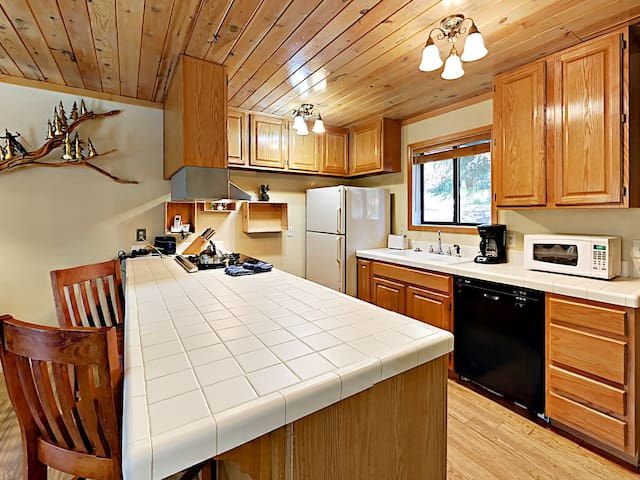 A fully stocked kitchen with dual sinks and a gas range
