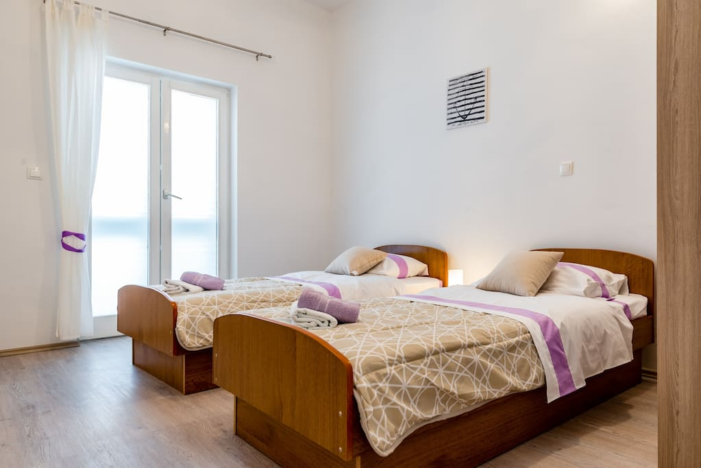 Bedroom with 2 singles and direct access to the balcony