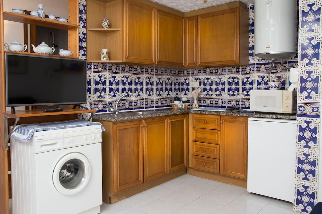 Cocina equipada con nevera, microondas y lavadora