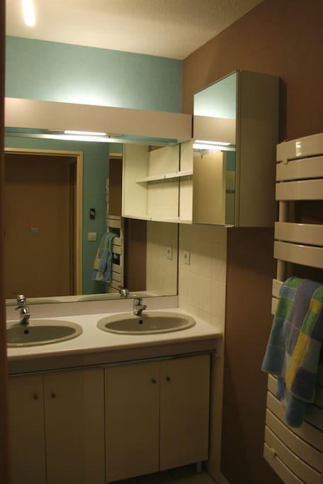 Sale de bain avec baignoire et double vasques.