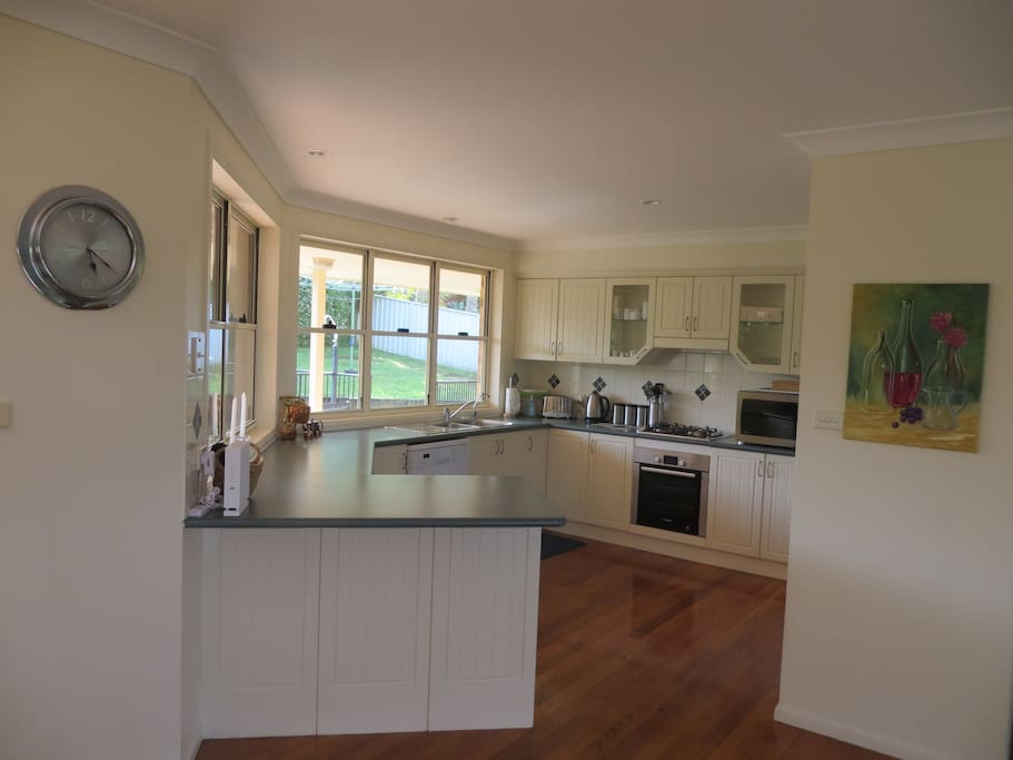 Fully fitted kitchen with view from two large windows of the pool area