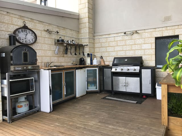 Under cover alfresco kitchen complete with kettle, toaster, coffee pod machine, barbecue with hood, hotplate, refrigerator, sink, microwave and pizza oven.  There are also saucepans, cooking utensils, crockery and cutlery.