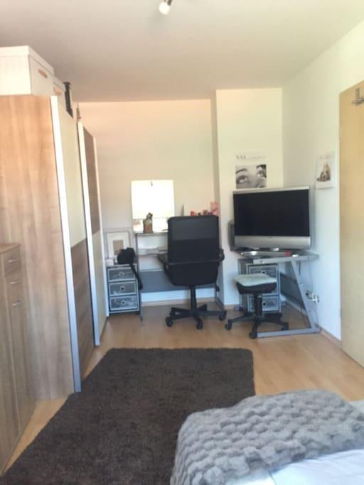 Schrank, Schreibtisch und großer Fernseher