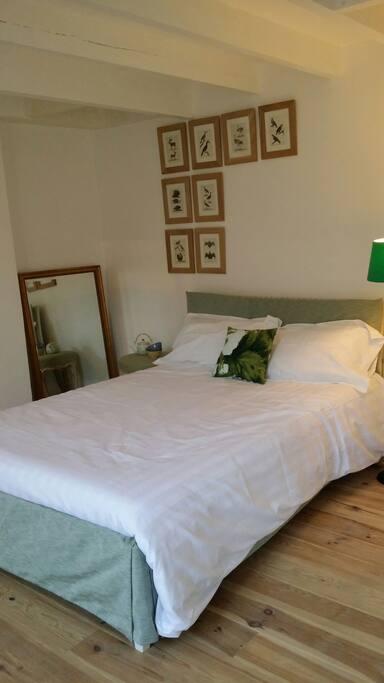 Grand lit double ambiance chaleureuse et confortable