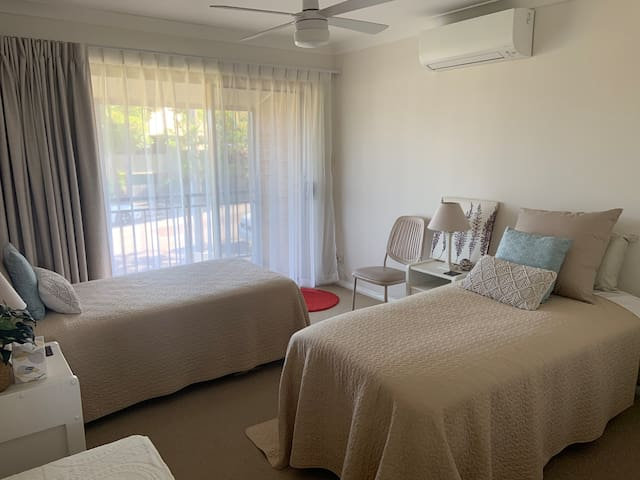 Second bedroom with two single beds, air conditioner  and access to balcony.