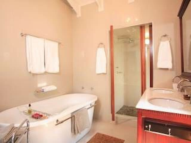 Main bedroom en-suite bathroom with shower and bath as well as double washbasin