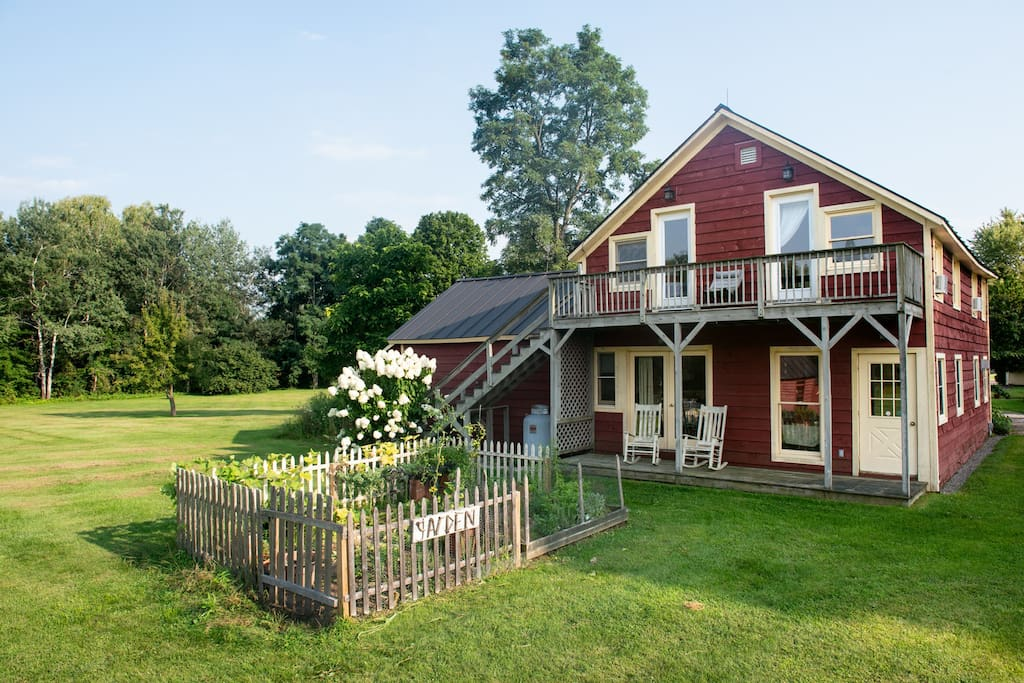 Rear of guest house with vegetable garden, small porch and balcony.