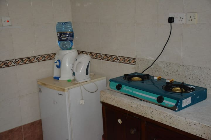 Kitchen with fridge, gas and mineral drinking water