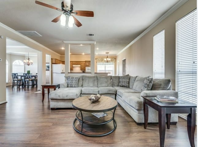 Open Living room area with large sectional and lots of windows for natural light
