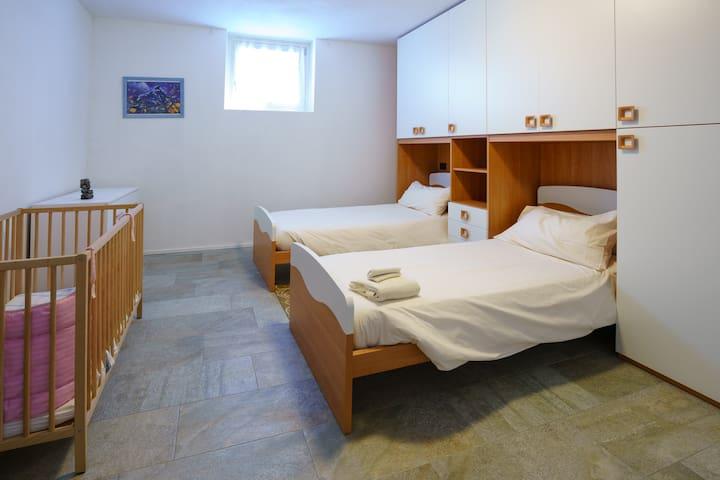 la camera con due lettini e la culla