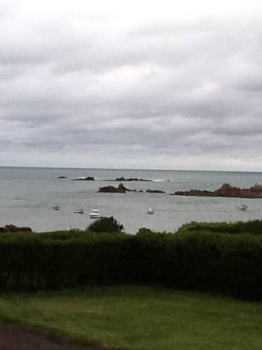 Les nuages bas, la mer au bout du chemin, les bateaux au mouillage: la Bretagne. Vue de la terrasse.