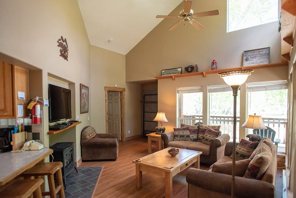 Spacious living room with vaulted ceilings, expansive windows, sleeper sofa, Murphy bed, gas fireplace and TV