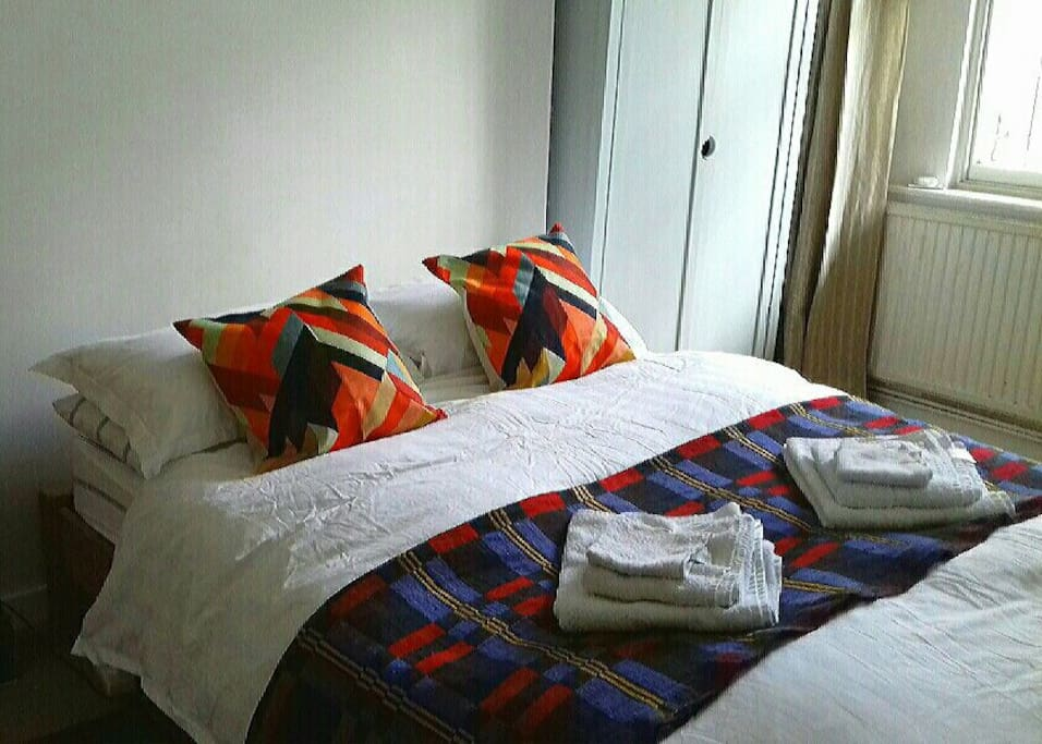 Comfortable standard double bed with cotton sheets.