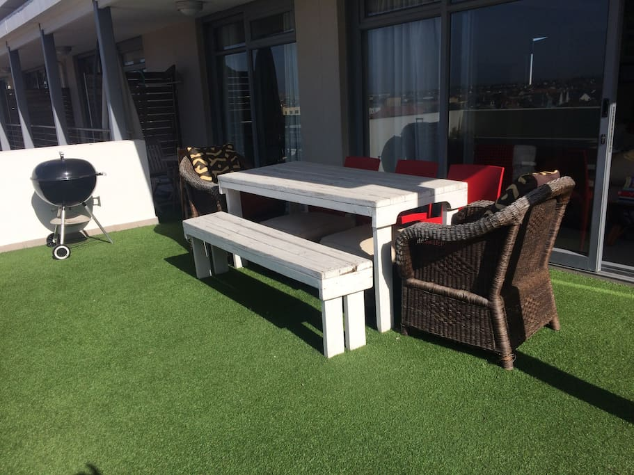 Large astro-turf terrace with seating area and BBQ facilities.