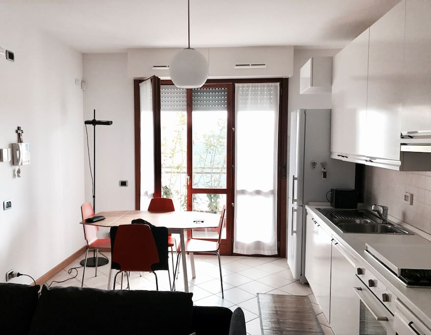 Kitchen with a balcony, fully equipped cooking space and dinner table