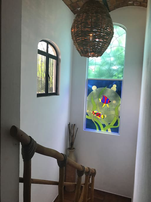 The main staircase features a large stained glass, custom pendant light  and railing by a local artisan.