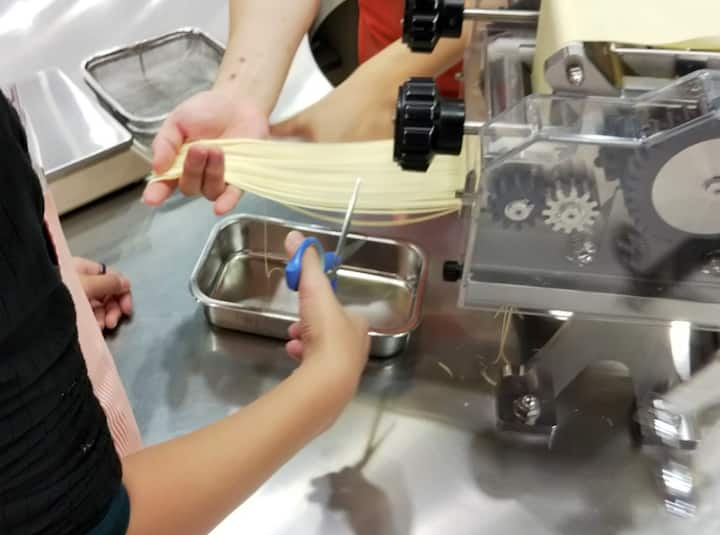 pressing into noodle strands and cutting