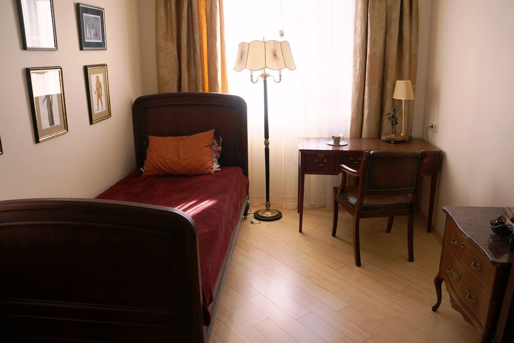 A guest bedroom with an authentic old furniture. Very stylish and relaxing. Perfect colors and lighting