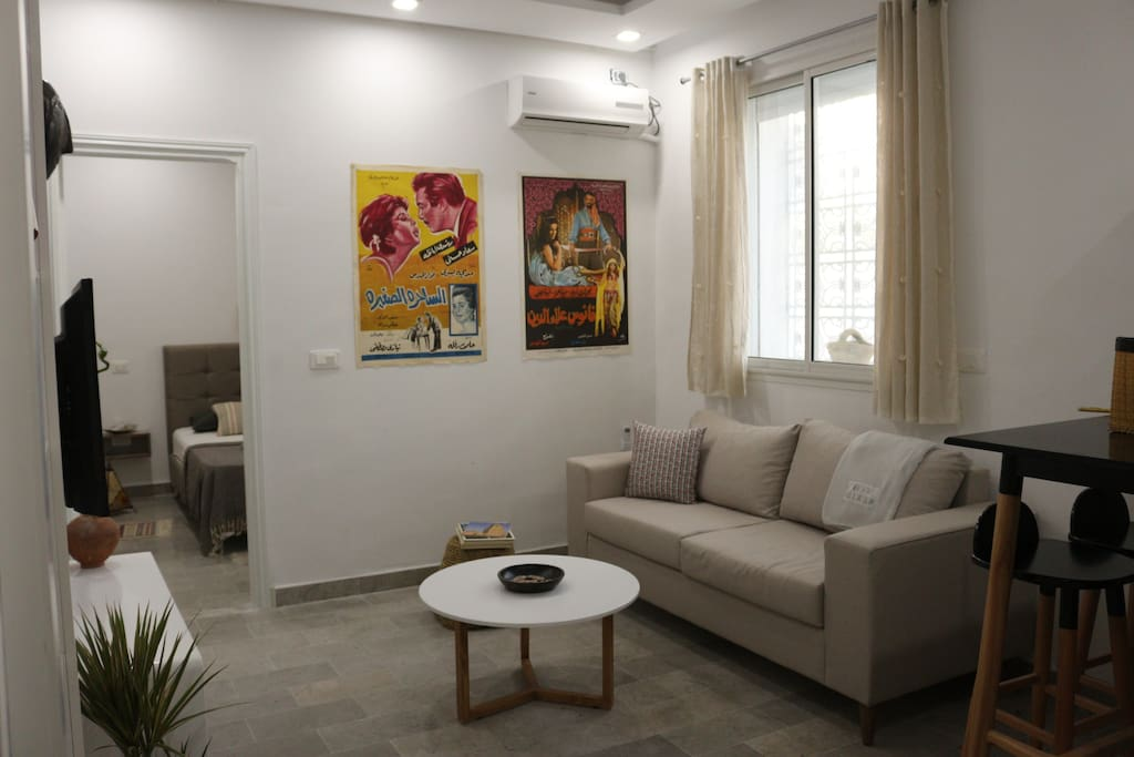 Salon lumineux avec canapé et table haute avec tabouret