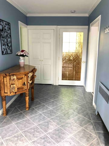 A large entrance hall with privacy film on French glass doors leading to a split staircase and owners residence. A large closet to store your suitcases and extras