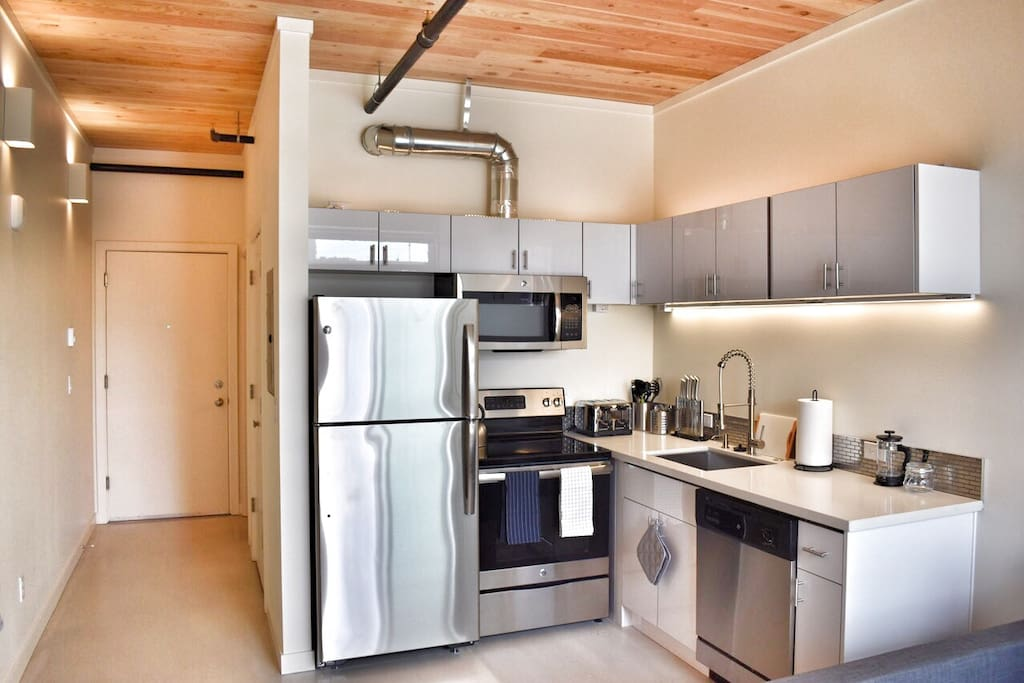 Chef's kitchen with Brand new stainless steel appliances, quartz countertops and concrete floors.
