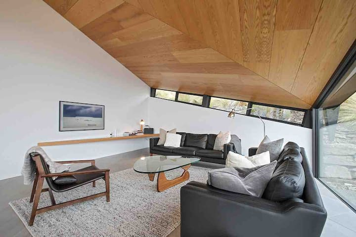 The lounge is cosy with a television perfectly placed for chilling out near the fire. The angular windows are replicated in the striking suspended and angled shelf.
