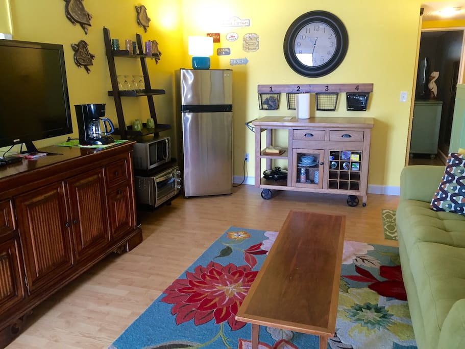 Living room/kitchenette with coffee maker, convection oven, induction burner, electric grill, microwave,  refrigerator, and all the cookware and dishes you'll need (incl. corkscrew!).