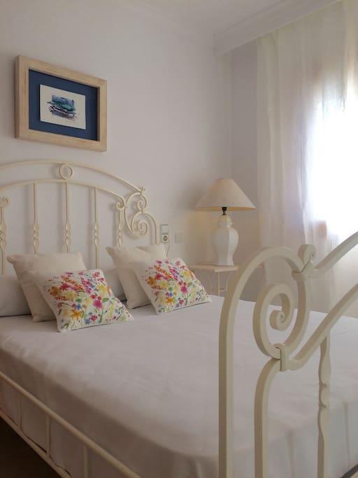 Dormitorio principal con armario empotrado, caja fuerte y vistas al jardín privado.