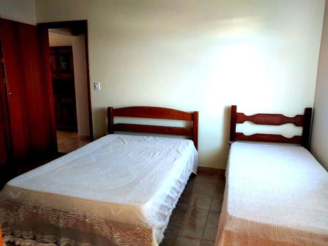 Suíte 1. 1 Cama de casal, 1 cama de solteiro, guarda-roupas com cabide, toalhas, lençois e cobertores.  Smart TV, banheiro privativo.