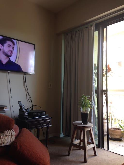Sala com sofá e TV é vista varanda