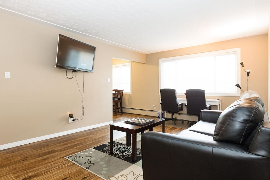 "Large living room with sofa bed + Executive office chairs and desk + Free Unlimited High Speed Wifi for streaming free Netflix movies on 50"" flat TV with Roku 3."