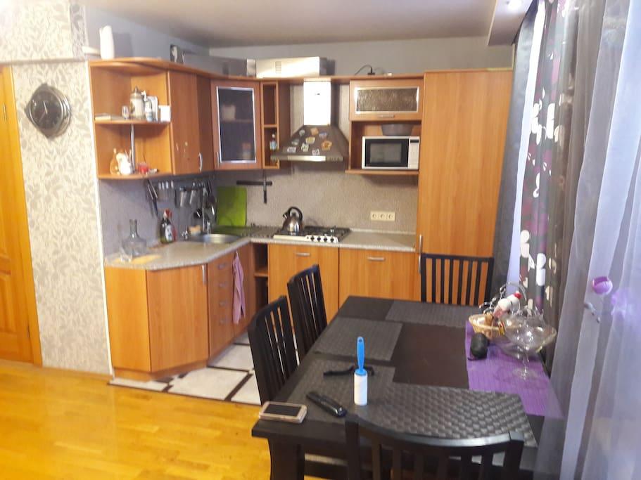 На кухне: посуда, газовая плита, микроволновая печь, холодильник.