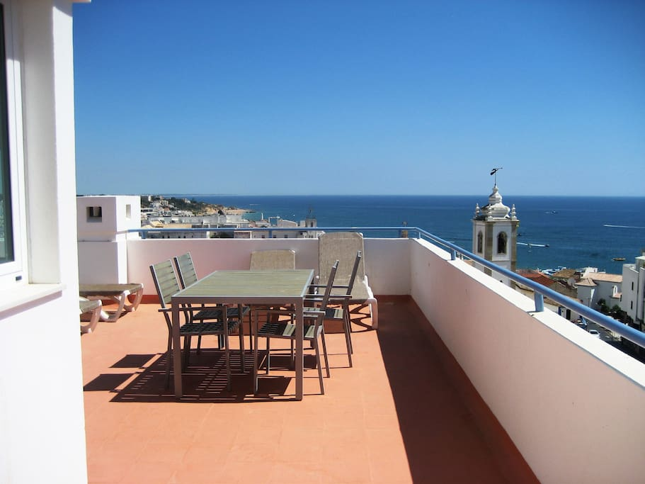 Terrace with sea view, sun beds, table, and shade