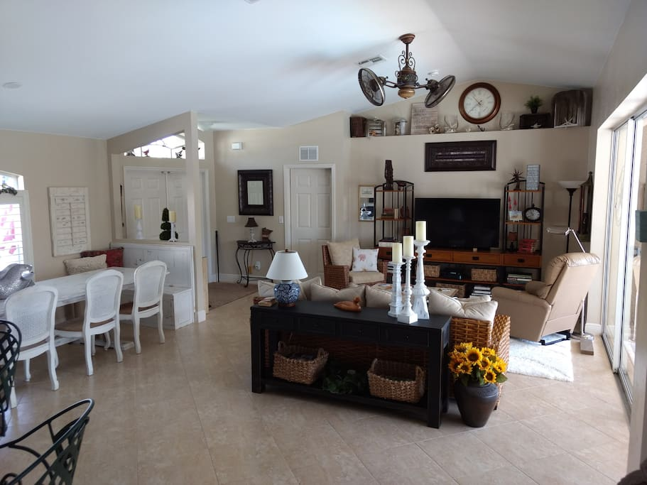 Great room towards front entrance and master suite with dining area to left and pool/lanai to the right.