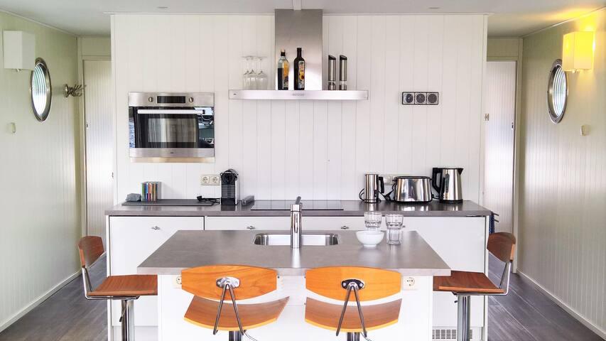 Küche mit Theke, vier Stühlen und allen Elektrogeräten: Herd, Ofen, Nespresso, Wasserkocher, Toaster, Milchaufschäumer, Spülmaschine