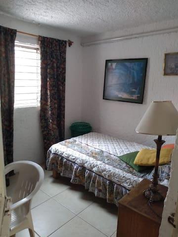 Habitación con una cama individual, tiene escritorio, una cómoda, sin clóset se puede colgar ropa en otro mueble afuera del cuarto, cuenta con dos baños compartidos, usualmente es una habitación fresca porque se encuentra junto a terraza/patio