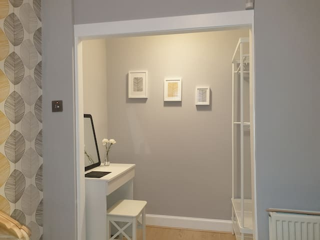 Dressing area, with dressing table and mirror, and wardrobe space.